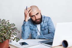 People, career, business and success concept. A portrait of young uccessful bearded bald businessman wearing jean shirt being tire stock photography