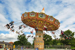 People on carousel under blue sky with clouds. Illustration of running carousel with people having fun, taken in Lightwater Valley amusement park, England, UK Royalty Free Stock Photo