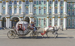 People in carriage at Palace Square near Winter Palace of St. Pe Stock Photos