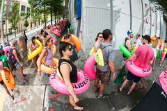 People Carry Innertubes And Wait In Line At Waterslide Event. Atlanta, GA, USA - July 15, 2017:  People carrying innertubes stand in a long line stretching Stock Photography