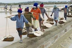 People carry salt  at the salt farmin Huahin, Thailand. Stock Photography