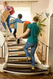 People carrying boxes upstairs. stock images