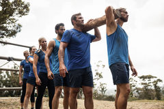 People carrying a heavy wooden log during boot camp Royalty Free Stock Photo