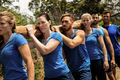 People carrying a heavy wooden log during boot camp Stock Photo