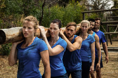 People carrying a heavy wooden log during boot camp Stock Photography