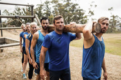 People carrying a heavy wooden log during boot camp Royalty Free Stock Image