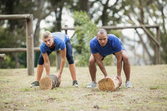 People carrying heavy wooden logs during obstacle course. In boot camp royalty free stock photos