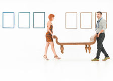People carrying a wooden bench Stock Image