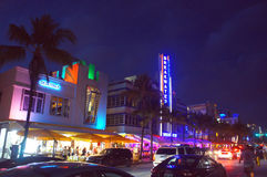 People and cars move alongside the night Ocean Drive street Stock Image