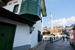 People and cars move on the narrow street with mosque and old Ottoman style house Royalty Free Stock Photos