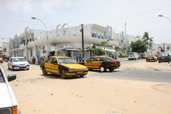 People and cars in a sandy street in the city of  Dakar in Seneg Stock Photos