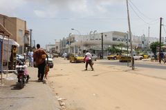People and cars in a sandy street in  city of  Dakar in Senegal Royalty Free Stock Photo