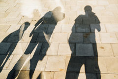 People casting shadows on the pavement Stock Photography