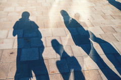 People casting shadows on the pavement Royalty Free Stock Photo