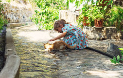 People and cat outdoors. Beautiful and happy little girl enjoyin Stock Images
