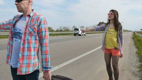 People catches the car hitchhiking. Father and daughter catching a car hitchhiking near the road. Two pleasant people stands near the road and show a sign of stock video footage