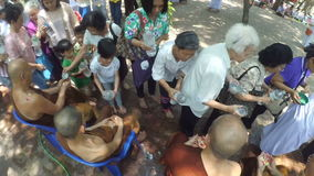 People celebrate Songkran by pouring water for buddhist priest and asking for blessings stock video
