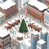People celebrating Christmas together. Happy people gathering together and celebrating Christmas in the city square around a tree under the snow Royalty Free Stock Images
