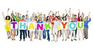 People Celebrating and Holding Word Thank You. Multi-ethnic group of arms outstretched people holding cardboards forming thank you Royalty Free Stock Image