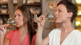 Women with gift drinking wine at bar or restaurant stock video
