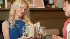 Women giving present to friend at wine bar stock footage