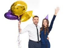 Happy couple with party caps and balloons Royalty Free Stock Photos