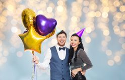 Couple with party caps and balloons over lights. People, celebration and holidays concept - happy couple with party caps and balloons over festive lights royalty free stock image