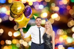 Happy couple with balloons over party lights. People, celebration and holidays concept - happy couple with party caps and balloons over festive lights background royalty free stock images