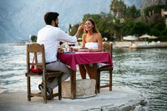 People, vacation, love and romance concept. Young couple enjoying a romantic dinner on beach. People, celebration, vacation, honeymoon and romance concept royalty free stock photography