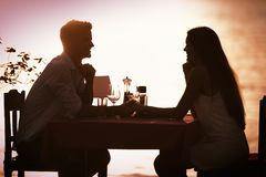 People, vacation, love and romance concept. Young couple enjoying a romantic dinner on beach. People, celebration, vacation, honeymoon and romance concept stock image