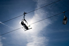 People in chairlift in front of bright sun Stock Photo
