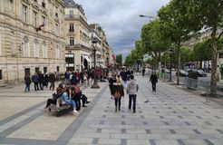 People on the Champs-Elysees in Paris, France. Paris, France - May 13, 2018: People walk on the Avenue des Champs-Elysees in Paris, France on May 13, 2018 royalty free stock images