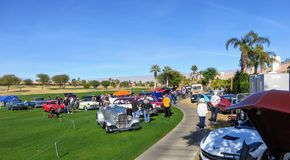People at charity car show admiring rows of classic, hot rod and special interest cars parked at a golf course in Palm Springs royalty free stock photography