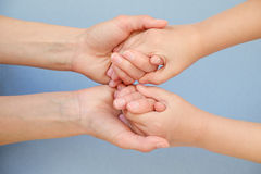 People, charity, family and care concept - close up of woman hands holding girl hands. On blue background stock image