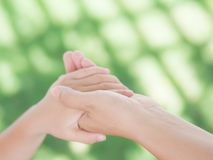 People, charity and family concept. Close up of woman  holds the hand of a lovely child. Mother and son holding hands in the background of the green field Stock Images