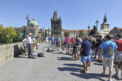 People on Charles Bridge, Prague. Tourists on the Charles Bridge in Prague listening to a band with street artists playing music to earn some money Royalty Free Stock Images