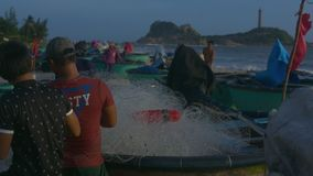 People Check Nets after Storm on Beach by Boats. NHA TRANG/VIETNAM - NOVEMBER 07 2017: Closeup people check fishing nets and look for holes after heavy storm on stock video