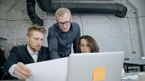 People checking document or agreement for new project. Concept of group people communication. Businessman standing near engineer man and mature woman in modern stock footage