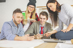 People checking phones. Young people in office taking on a break from work. They are checking their phones Royalty Free Stock Photography
