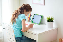 Girl with tablet pc writing to notebook at home Stock Photography