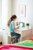Girl with tablet pc writing to notebook at home. People, children and education concept - happy girl with tablet pc computer writing to notebook at home Royalty Free Stock Photography