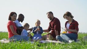 People with children having a rest on a picnic laugh and drink fruit water, slow motion. Black and white guys with two white girls and two children having a rest stock video footage