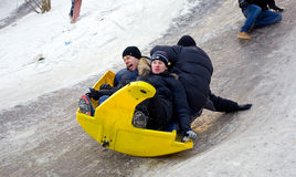 People Children ride on the winter snow sledding from hills. Winter playing, fun, snow Royalty Free Stock Photos
