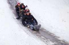 People Children ride on the winter snow sledding from hills. Winter playing, fun, snow Stock Photography