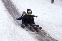 People Children ride on the winter snow sledding from hills. Winter playing, fun, snow Stock Images