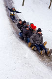 People Children ride on the winter snow sledding from hills. Winter playing, fun, snow Royalty Free Stock Image