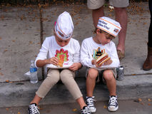 People, Children siting on curb with Hot Dogs Royalty Free Stock Photos