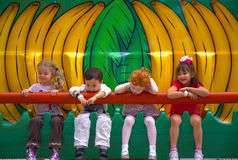 People-Children sitting on a Ride Smiling. Young Children sitting and making faces and smiling and having a good time on a ride Royalty Free Stock Images