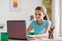 Girl typing on laptop at home Stock Images