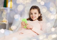 Happy girl lying in bed with smartphone at home. People, children and technology concept - happy smiling girl lying awake with smartphone in bed over holidays Stock Image